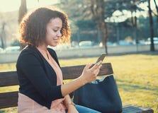 Mujer negra que usa el app en el teléfono móvil Foto de archivo