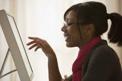 Mujer negra que usa el ordenador Fotos de archivo