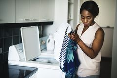 Mujer negra que usa la lavadora que hace el lavadero imagenes de archivo