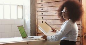 Mujer negra seria de la oficina que mira in camera y que pide que alguien tome un poco de papel metrajes
