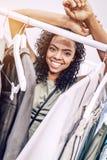 Mujer negra sonriente cerca de suspensiones en tienda Foto de archivo