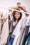 Mujer negra sonriente detrás del estante con ropa Imagen de archivo libre de regalías
