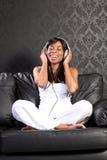 Mujer negra sonriente en el sofá que escucha la música Foto de archivo libre de regalías