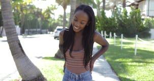 Mujer negra sonriente que ajusta el pelo metrajes