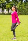 Mujer negra sonriente que estira la pierna al aire libre Fotografía de archivo