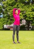 Mujer negra sonriente que estira la pierna al aire libre Foto de archivo