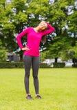 Mujer negra sonriente que estira la pierna al aire libre Foto de archivo libre de regalías