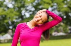 Mujer negra sonriente que estira la pierna al aire libre Imagen de archivo