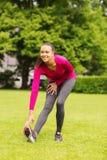 Mujer negra sonriente que estira la pierna al aire libre Imagen de archivo libre de regalías