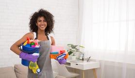 Mujer negra sonriente que presenta con las fuentes de limpieza imagen de archivo