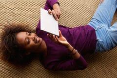 Mujer negra sonriente que se acuesta con la tableta digital Fotos de archivo libres de regalías