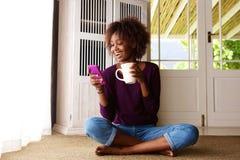 Mujer negra sonriente que se sienta en piso en casa con el teléfono celular Imagenes de archivo
