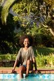 Mujer negra sonriente que se sienta por la piscina con los pies en agua Imagen de archivo