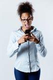 Mujer negra sorprendida que mira el móvil Fotos de archivo