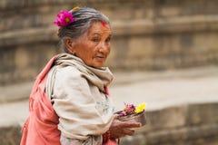 Mujer nepalesa que lleva ofrendas religiosas Foto de archivo