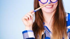 Mujer nerdy feliz en pluma de tenencia de los vidrios Imágenes de archivo libres de regalías