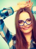 Mujer nerdy sonriente feliz en vidrios extraños Imágenes de archivo libres de regalías