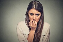Mujer nerviosa vacilante insegura ansiosa joven que muerde sus uñas Fotografía de archivo libre de regalías