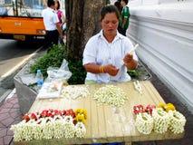 Mujer no identificada para hacer las guirnaldas de la flor en el estilo tailandés para la venta a la adoración en Wat Sutat Foto de archivo libre de regalías