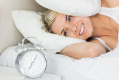 Mujer oídos de una cubierta con la almohada como ella mira el despertador Fotos de archivo libres de regalías