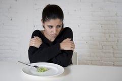 Mujer o adolescente con la bifurcación que come el plato con pequeña lechuga ridícula como su símbolo de la comida de la dieta lo Imagenes de archivo