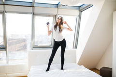 Mujer o adolescente en auriculares que escucha la música del smartphone, cantando y bailando en cama en casa Fotos de archivo