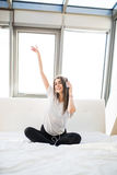 mujer o adolescente en auriculares que escucha la música del smartphone y que baila en cama en casa Fotografía de archivo libre de regalías