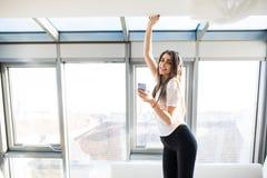 Mujer o adolescente feliz en auriculares que escucha la música del smartphone Imágenes de archivo libres de regalías