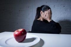 Mujer o adolescente joven con la fruta de la manzana en plato como símbolo de la dieta loca en trastorno alimenticio Fotos de archivo