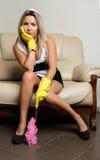 Mujer o ama de casa aburrida que se sienta en un sofá principal con los guantes de goma imágenes de archivo libres de regalías