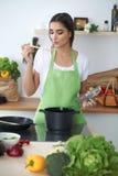 Mujer o estudiante hispánica joven que cocina en cocina Fotografía de archivo