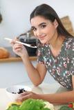 Mujer o estudiante hispánica joven que cocina en cocina Muchacha que prueba la ensalada fresca mientras que se sienta en la tabla imagen de archivo