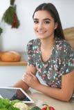 Mujer o estudiante hispánica joven que cocina en cocina Muchacha que usa la tableta para hacer compras en línea o para encontrar  Foto de archivo