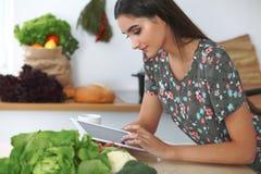 Mujer o estudiante hispánica joven que cocina en cocina Muchacha que usa la tableta para hacer compras en línea o para encontrar  foto de archivo libre de regalías