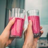 Mujer o mano de la sacudida con la consumición de concepto sano rosado del smoothie de la baya en fondo de la pared Comida vegeta imagen de archivo