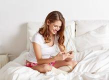 Mujer o muchacha feliz con smartphone en cama en casa Imagen de archivo libre de regalías