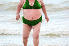 Mujer obesa en la playa Imagenes de archivo