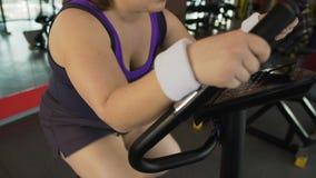Mujer obesa motivada que trabaja difícilmente en la bici inmóvil en el gimnasio, pérdida de peso almacen de video