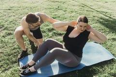 Mujer obesa que hace sentar-UPS con el instructor personal imagenes de archivo