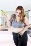 Mujer obesa que mide su vientre en el gimnasio Foto de archivo