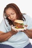 Mujer obesa que mira la hamburguesa Imagenes de archivo