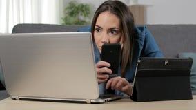 Mujer obsesionada que usa los dispositivos múltiples en casa metrajes