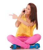 Mujer ocasional asentada que habla en el teléfono y señalar Foto de archivo libre de regalías