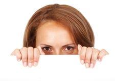Mujer ocasional que mira furtivamente sobre una cartelera Fotos de archivo libres de regalías