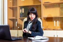 Mujer ocupada en la oficina que mira su reloj Imagen de archivo