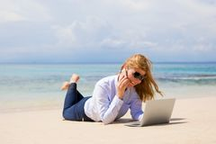 Mujer ocupada que disfruta del trabajo de la playa imagen de archivo