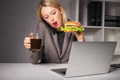 Mujer ocupada que habla en el teléfono mientras que comiendo la hamburguesa y el café imagenes de archivo