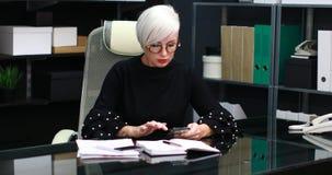 Mujer ocupada que habla en móvil y línea horizonte que se sienta en la tabla en oficina almacen de video