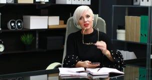 Mujer ocupada que habla en móvil y línea horizonte que se sienta en la tabla en oficina almacen de metraje de vídeo