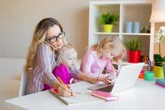 Mujer ocupada que intenta trabajar mientras que cuida a niños a dos niños imagenes de archivo